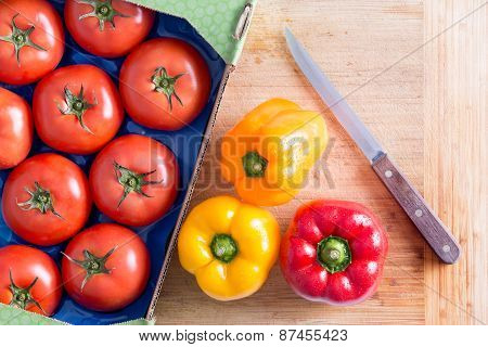 Tomatoes And Bell Peppers On Top Of Chopping Board