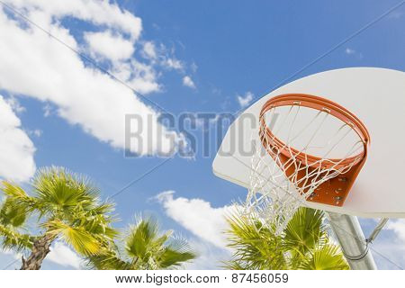Abstract of Community Basketball Hoop and Net and Palm Trees Against Blue Sky.