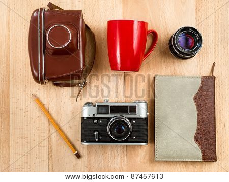 Retro Journalist Workspace With Camera, Lens, Notebook, Pencil And Cup