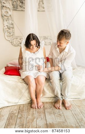 Pregnant Couple Sitting On Bed And Holding Copy Space Sign On Abdomen