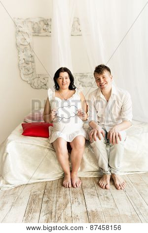 Happy Pregnant Couple Sitting On Bed With Copy Space Paper Sign