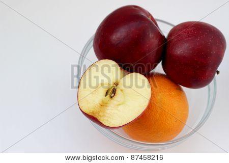 Apples and orange in vase