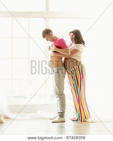 Funny Shot Of Pregnant Wife Hugging Husband With Big Abdomen
