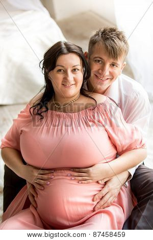 Portrait Of Handsome Man Hugging Pregnant Wife From Back