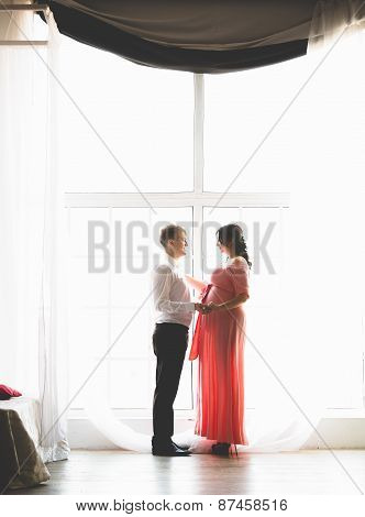 Handsome Man And Cute Pregnant Wife Standing Next To Big Window