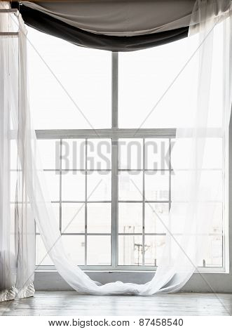 High Window From Ceiling To Floor With Long White Curtains