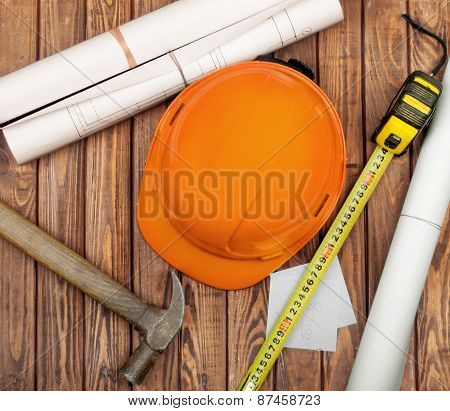 Hammer, Folding Ruler, Blueprint And Yellow Safety Helmet On Wooden Background