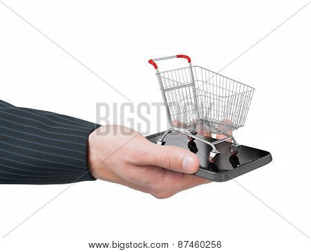 Man Hand Holding Smartphone With Shopping Cart. E-commerce Concept.