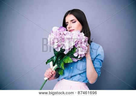 Young beautiful woman smelling flowers over gray background