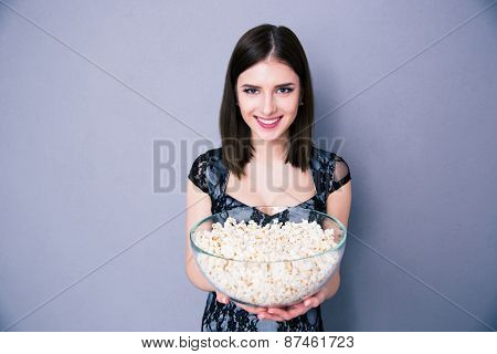 Happy young woman holding bowl of popcorn over gray background, looking at camera