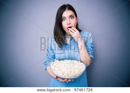 Young surprised woman eating popcorn over gray background. Looking at camera