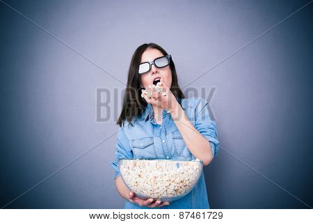 Cute woman in cinema glasses eating popcorn over gray background