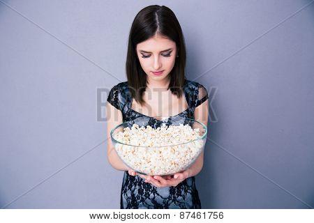 Young woman holding bowl of popcorn over gray background