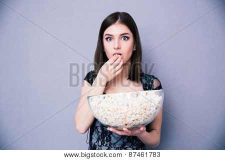 Young amazed woman eating popcorn over gray background. Looking at camera