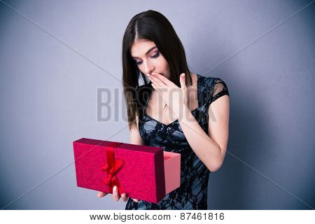 Amazed woman opening gift box over gray background. Wearing in dress. Looking on present