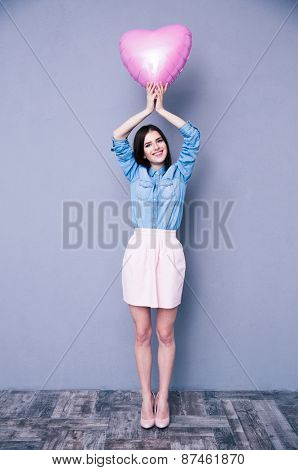 Full length portrait of a happy charming woman holding heart shaped balloon over gray background. Looking at camera