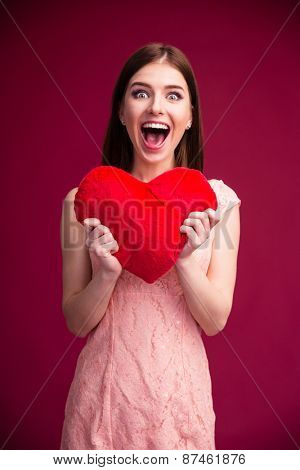 Surprised woman holding red heart over pink background. Looking at camera