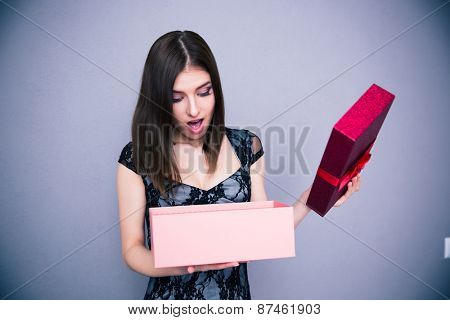 Happy surprised woman opening gift box over gray background. Wearing in dress. Looking on present