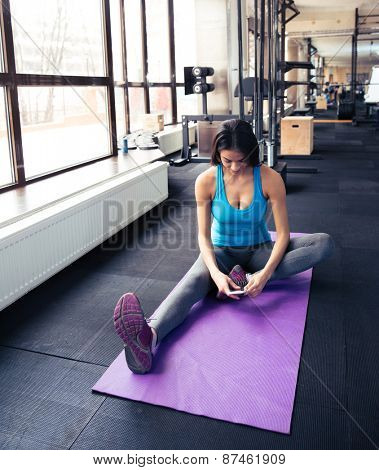 Young woman sitting on the yoga mat and using smartphone at gym