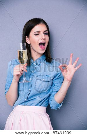 Attractive young woman holding glass of champagne. Showing ok gesture and winking. Standing over gray background