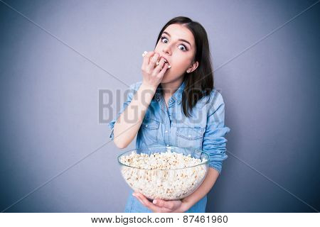 Young cute woman eating popcorn over gray background. Looking at camera