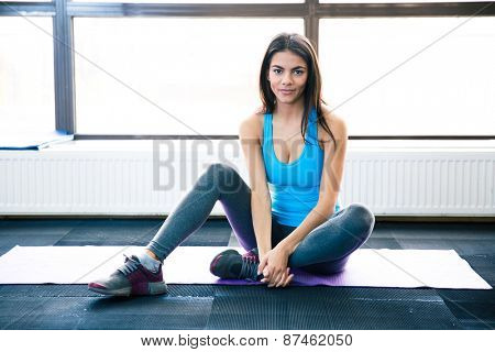 Thoughtful fit woman sitting on yoga mat and looking at camera