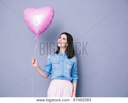 Happy woman holding balloon over gray background. Lookign away.
