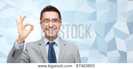 business, people, vision and office concept - happy smiling businessman in eyeglasses and suit showing ok gesture over gray graphic low poly background