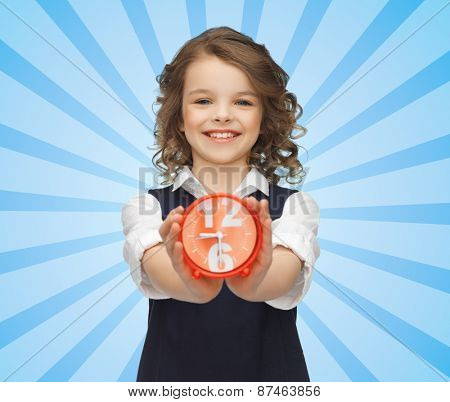 people, childhood, time and punctuality concept - happy girl with alarm clock over blue burst rays background