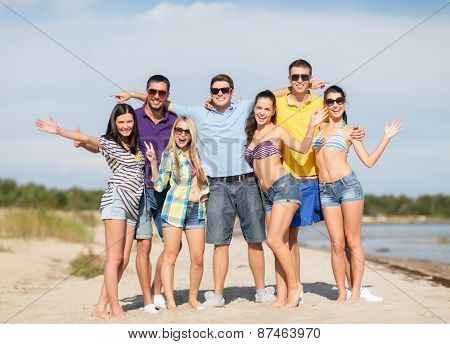 summer holidays, tourism, travel, gesture and people concept - group of happy friends in sunglasses waving hands on beach