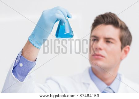 Scientist looking attentively at the beaker in laboratory