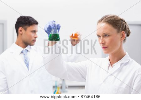 Concentrated scientists holding beakers with fluid in laboratory