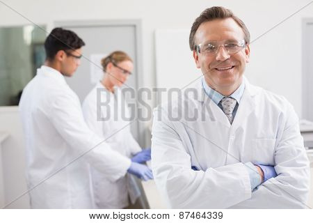 Smiling scientist looking at camera while colleagues working behind in laboratory