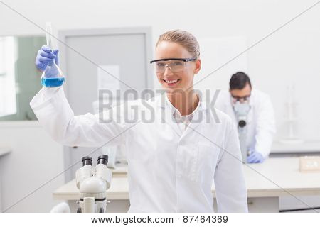 Scientist examining blue precipitate in baker in the laboratory