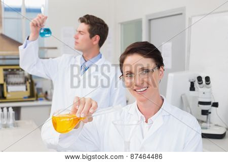 Scientists working attentively together with beakers in laboratory