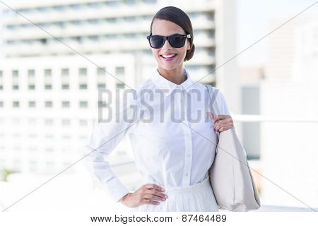 Pretty woman looking at camera with hand on hips outside