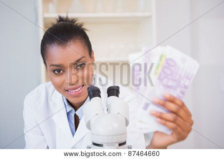 Smiling scientist holding money and looking at camera in laboratory