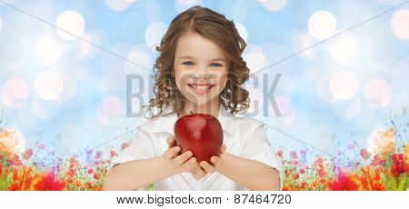 people, children, healthy eating, summer and food concept- happy girl holding red apple over blue sky and poppies field n background