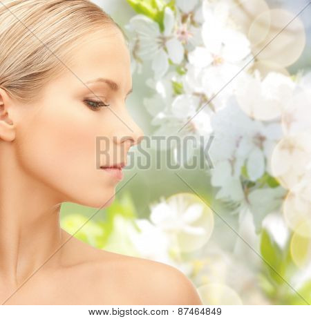 beauty, people, summer, spring and health concept - beautiful young woman face over green blooming garden background