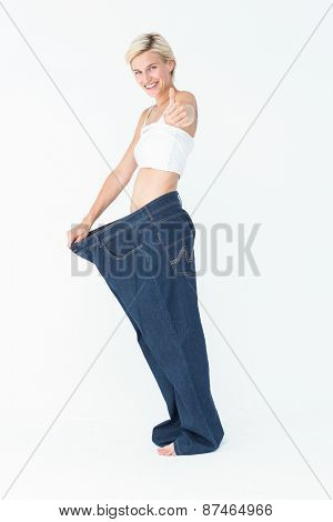 Blonde wearing too large pants with the thumb up on white background