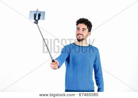 Casual man using a selfie stick shot in studio