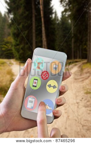 Hand holding smartphone against narrow dirt road leading to two different track along trees