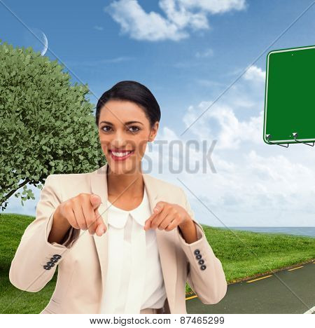 Smiling businesswoman pointing at the camera against road leading out to the horizon