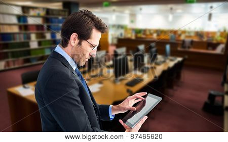 Businessman standing while using a tablet pc against computer desks in the library