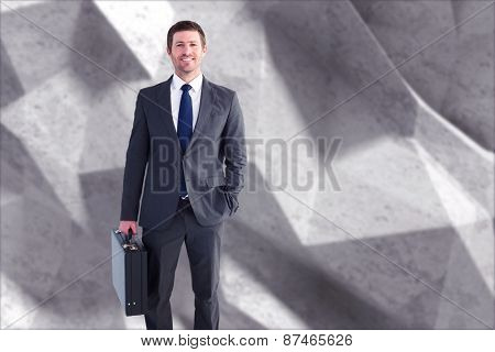 Businessman standing with his briefcase against grey angular background