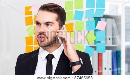 Smart businessman speaking on the phone against closeup of colorful sticky notes at office