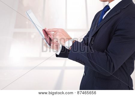 Businessman in suit using digital tablet against bright white room with windows