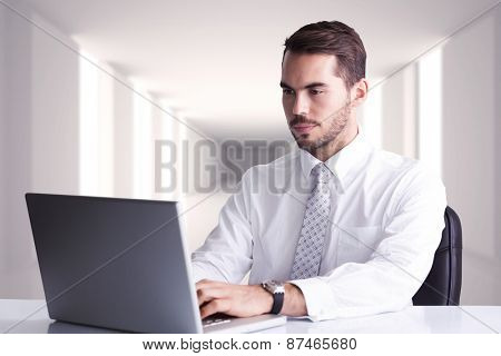 Cheerful businessman using laptop at desk against digitally generated room