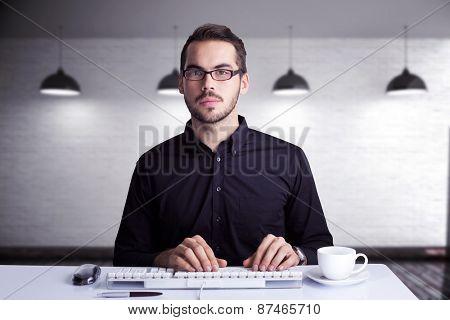 Focused businessman typing on keyboard against grey room