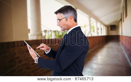 Mid section of a businessman touching tablet against hallway